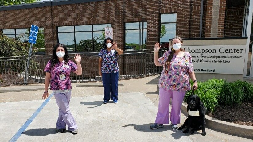 a picture of three nurses wearing masks waving hello