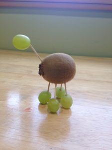 a food sculpture of kiwi and grapes