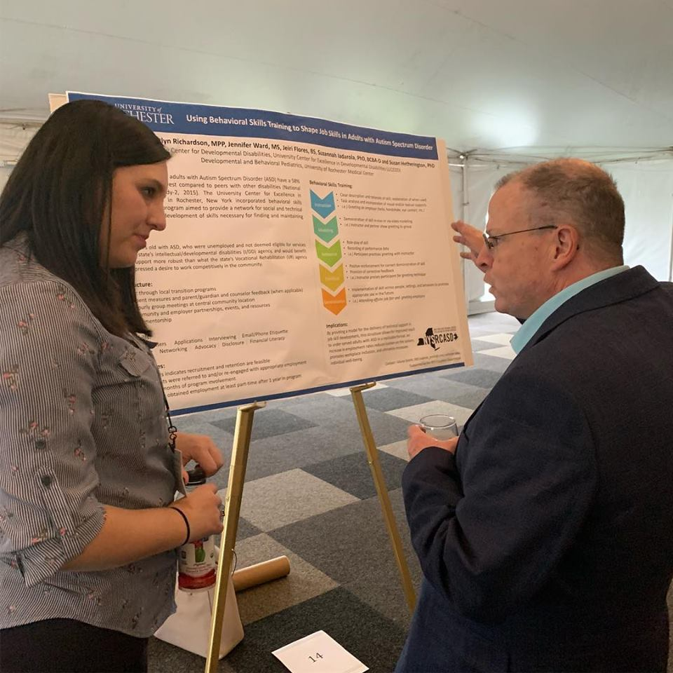 a women and a man have a discussion in front of a poster