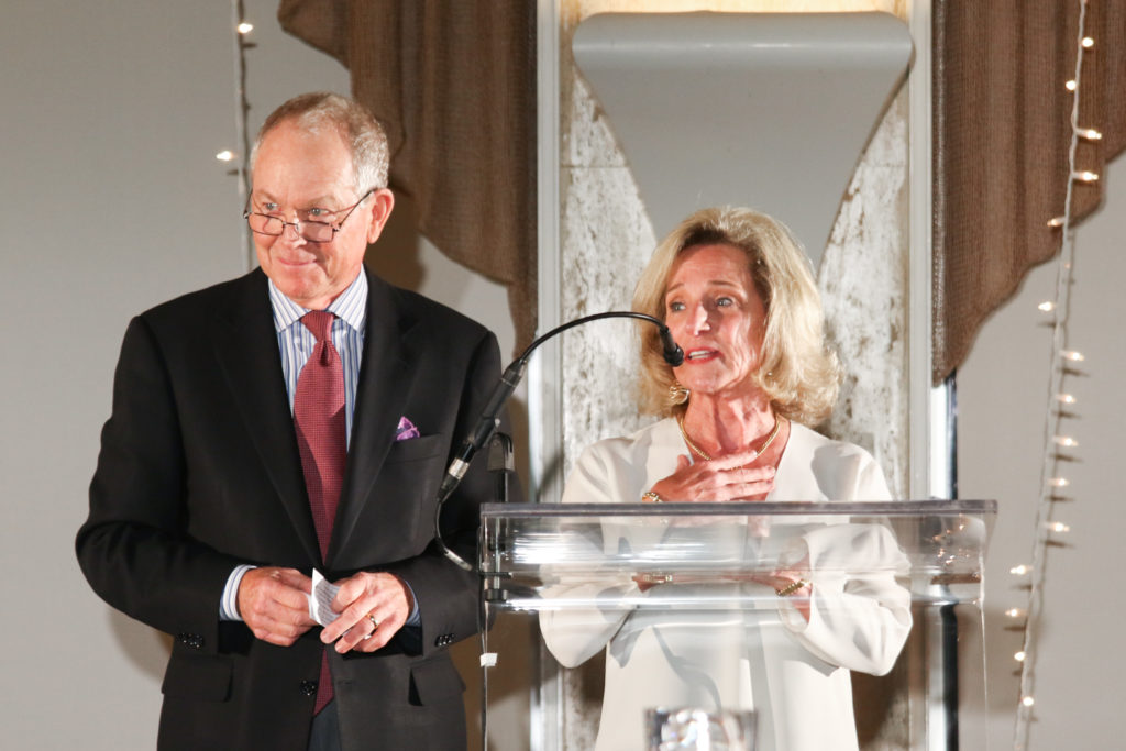 A picture of Bill and Nancy Thompson speaking at a lectern.