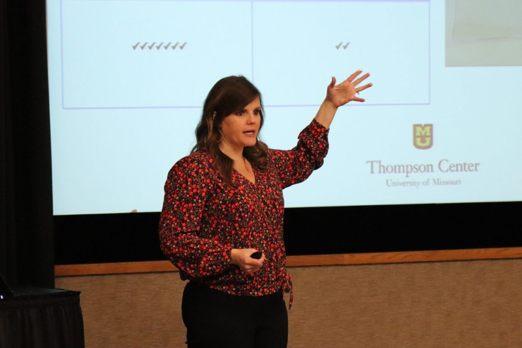 a women gives a presentation in front of a projector