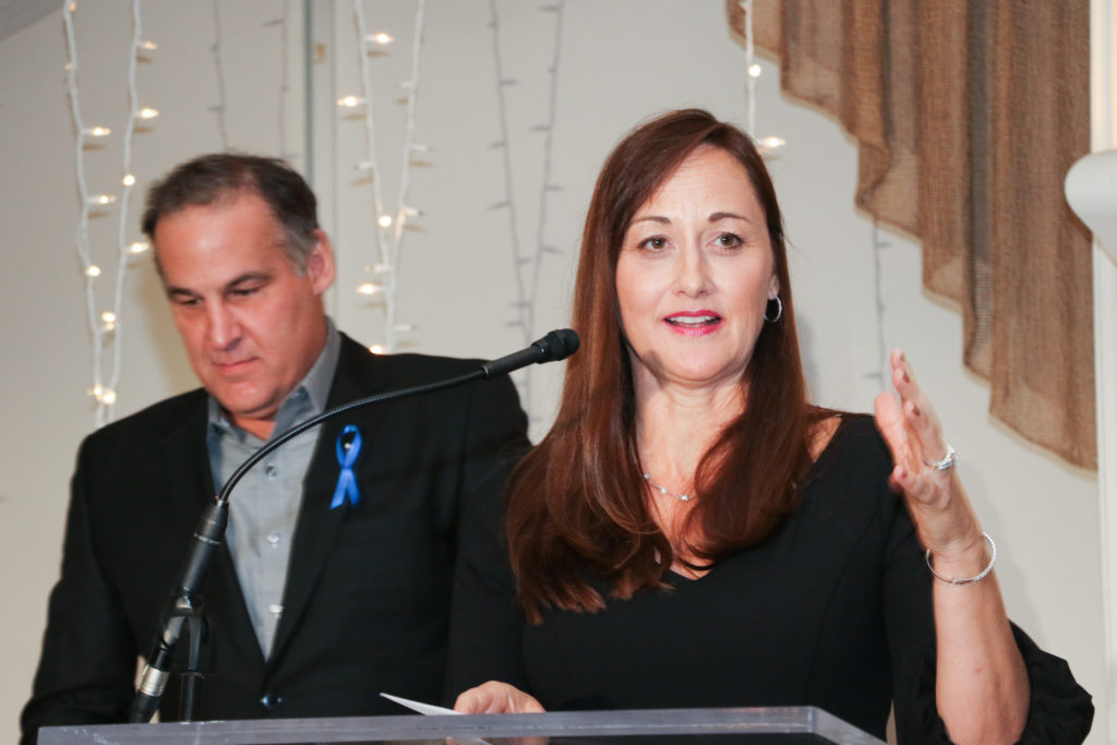 Sue Mellanby speaking at a lectern with her husband standing behind her.
