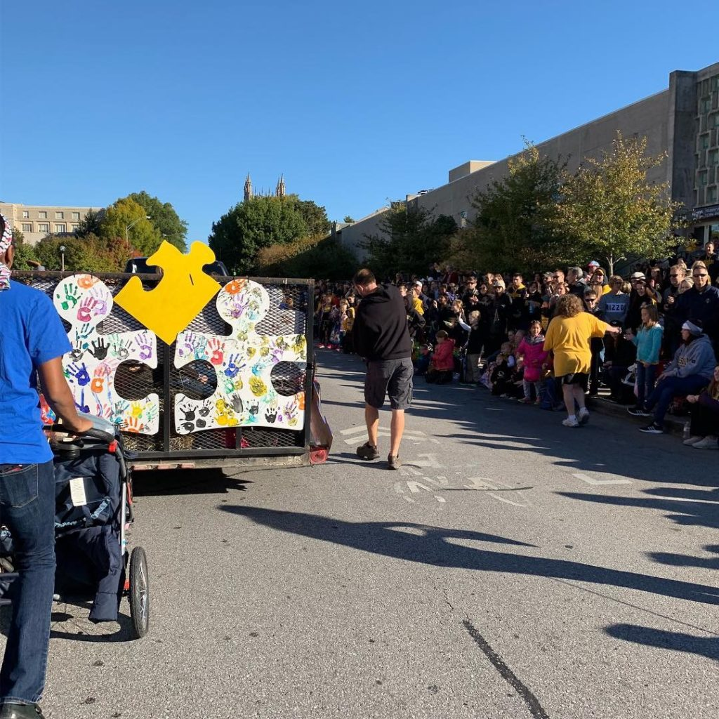 a picture of children and parents riding a trailer covered in painted puzzle pieces