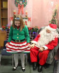 Sam showing off her dress to Santa