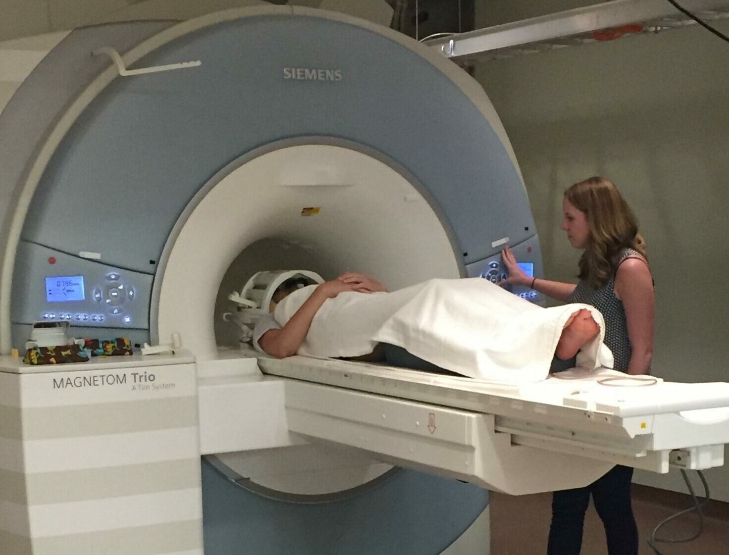 a woman puts a patient into the MRI