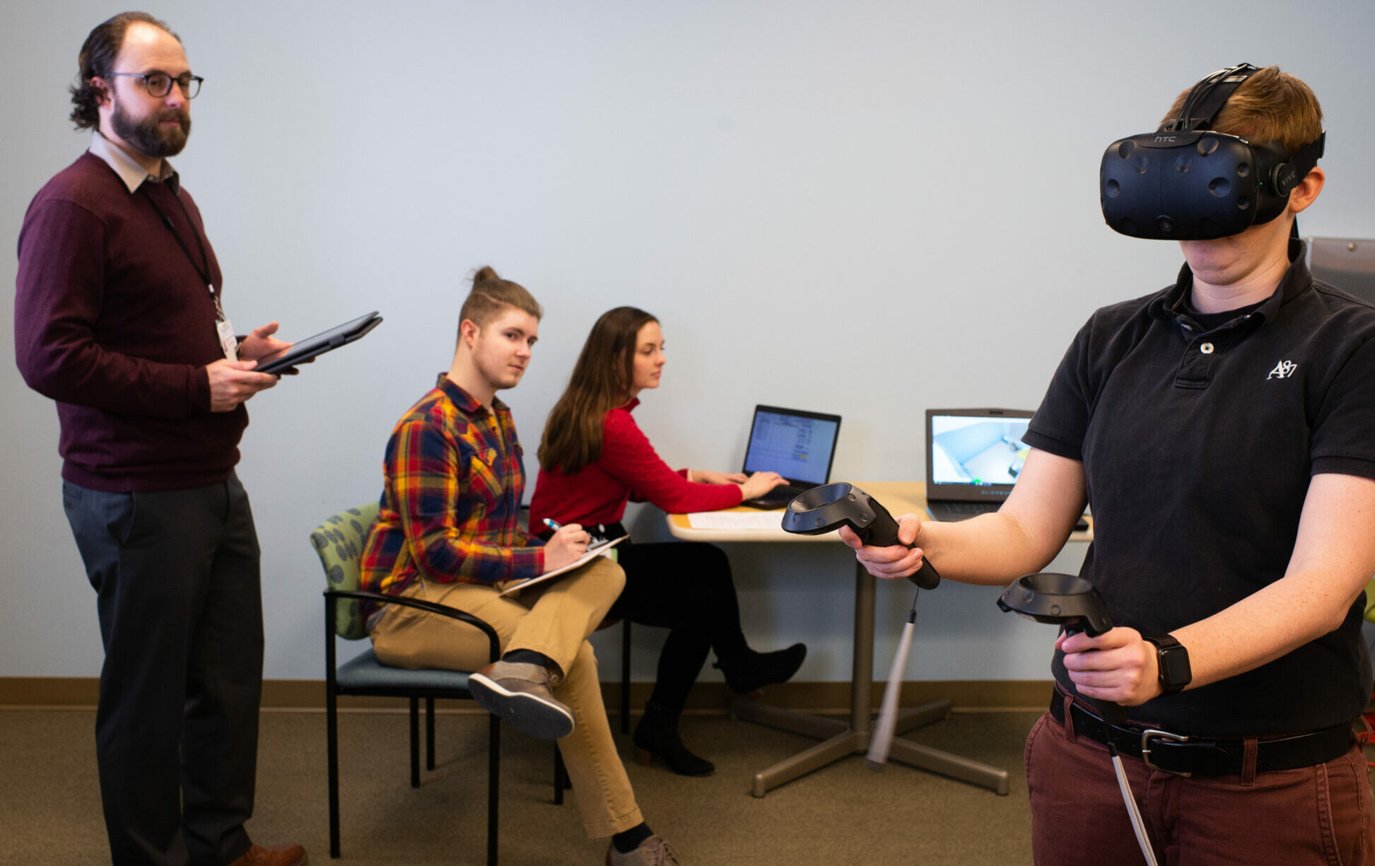 A photo of Dr. Clay watching a student train on the virtual reality simulator