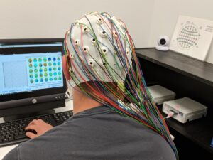 a picture of a man wearing an EEG cap with wires coming from it