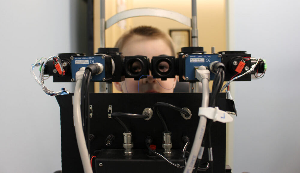 a picture of a boy looking through visual testing equipment