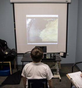 a boy views images in front of an eye tracker