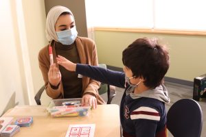 a picture of Basmah Alshatti working with a young boy
